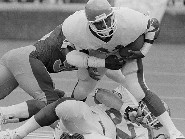 New Jersey Generals Herschel Walker steps over teammate Dave Lapham as he's held by Stars' George Cooper in the first quarter of their USFL playoff game.